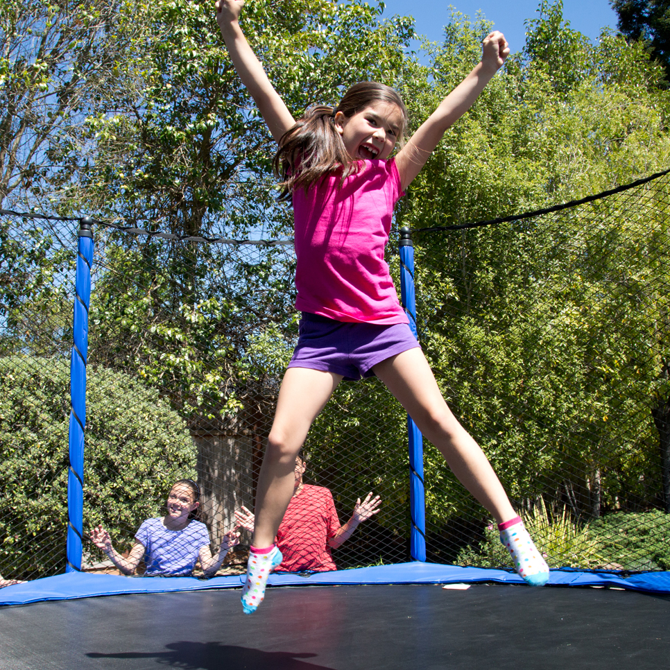 trampoline-benefit-active-kids-Girl-in-pink-jumping-backyard-trampoline