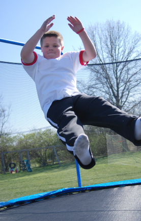 boy-jumps-safely-with-outdoor-trampoline-safety-net-enclosure